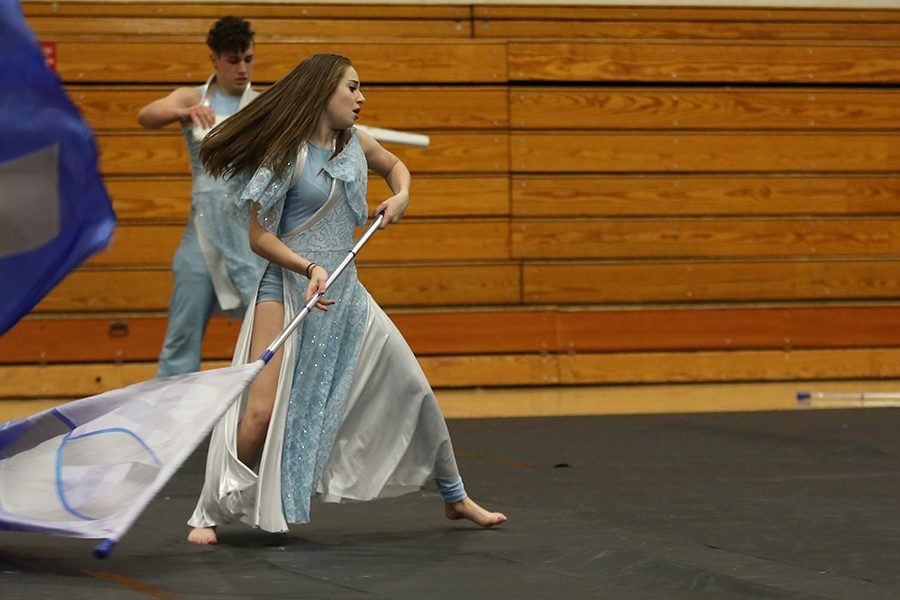 """Last competition approaching, Sarah Lawson (10) performs her winter guard state performance routine for the parents during practice, April 5. """"I joined winter guard to be a part of a team,"""" Lawson said. """"The best part about it is how close we are. We are like a unit. The competitive aspect is also nice, but mostly just being with all these people."""" Winter guard will be competing at state April 7th at Ozark High School in Ozark, MO."""