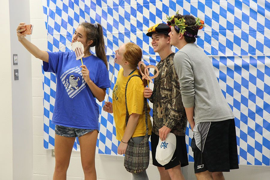 Jordan Thompson (12). Riley Schaefer (12), Bryan Howard (12) and Zach Walls (12)  capture the German culture around them at Rocktoberfest in the Commons, Oct. 3.