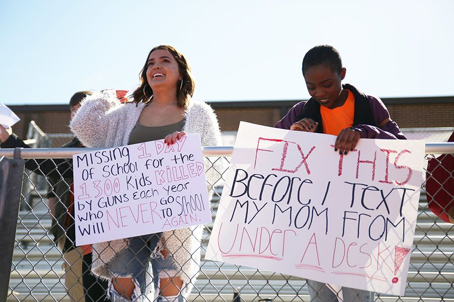 Grace Eickel and Sophana Holdegraver (12) hold up signs during the EHS walkout, April 20.