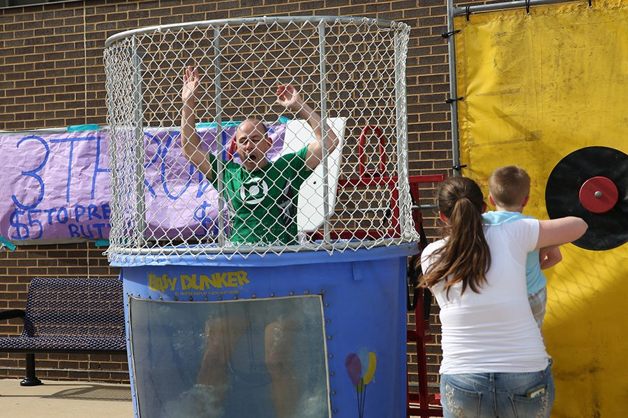 "Dunked for a cause, Andy Gensler, language arts, gets dunked during the BBQ fundraiser for Carolyn Baremore, science, May 11. ""Mrs. Baremore is awesome,"" Gensler said. ""If I could pick a spirit animal, it would be Mrs. Baremore. She just brings so much enthusiasm for life and teaching. The number of kids I have had who have told me she connected with them when no one else was able to is remarkable. She is amazing and anything we could do to support her needed to be done. I just liked to see the outpouring support from the community. It was great to see so many people show up on a Friday afternoon to me and is just a powerful expression of caring and love. Eureka sees people come together to help each other as often as they can. Whether it is something school-sponsored, like a canned food drive, where people don't have to but want to, just give to help the community or sandbagging with the floods. Anytime anyone is in need, I have never heard of another school who responds so quickly and generously."" The community raised enough to meet two year's worth of out-of-pocket expenses to support her ongoing treatment."