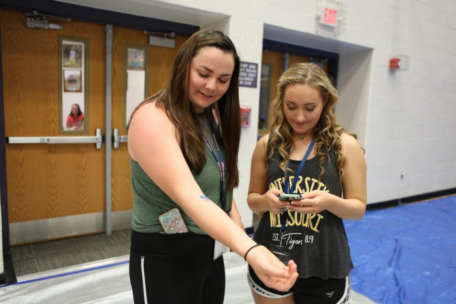 Shelby Wright and Madison Ripson inspect their temporary tattoos at the Senior Celebration, May 24.