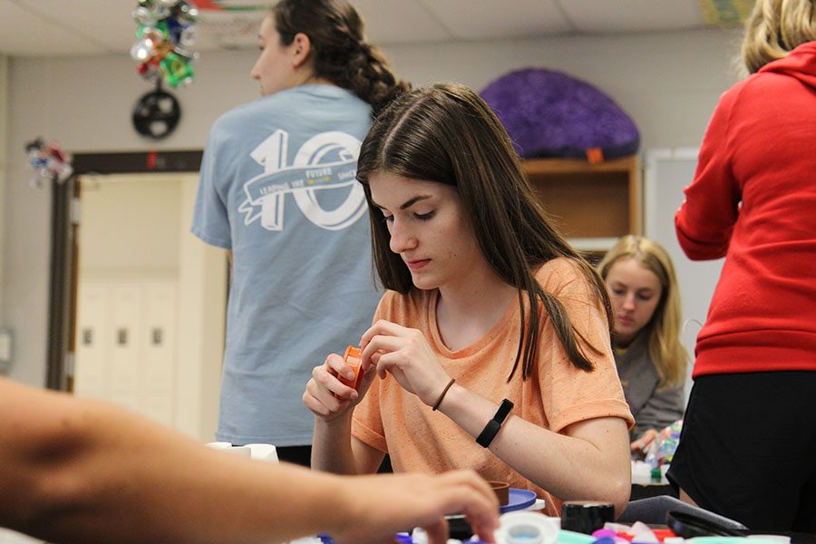 "Bottle caps surrounding her, Emma Dill (12) sorts the bottle caps National Honors Society collected throughout last school year, Aug. 30. ""NHS is a great opportunity to get involved in the community and get to know people in various grade levels,"" Dill said. ""It allows you to know people in this school which is difficult because the school is big. Staying after was fun because we got to listen to some music and I got to hang out with people I hadn't seen since the end of last year."" The bottle caps will be melted down and transformed into benches to use in the outdoor classroom which will be behind the practice football field."