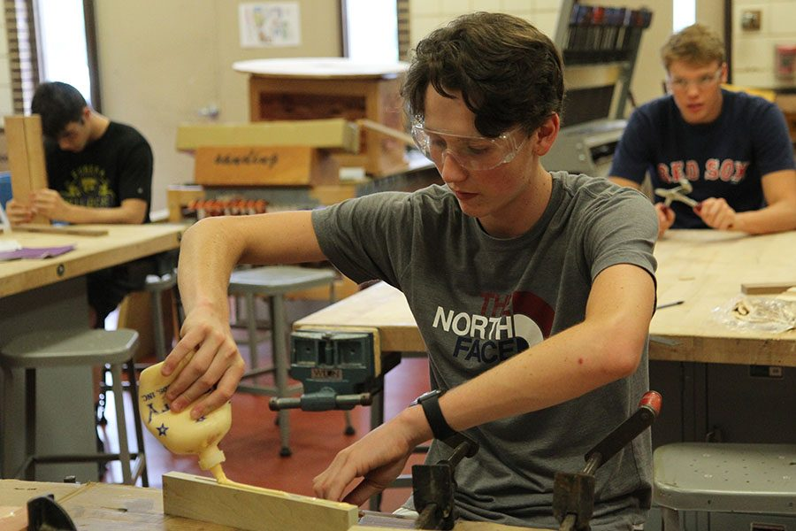 """Super glue in his hand, Willem Smith (12) builds his bench and table combination during David Luecke's sixth hour Woods 2 class, Aug. 31. """"I like how in Woods 2 you get more freedom,"""" Smith said. """"In Woods 1, our projects were scripted and you had to do them. In Woods 2, you make your own project and work on it at your own pace. You can do whatever you need to do. I decided to make a bench, but the back folds up to become a table. I decided to make something like that because I saw that my neighbor had one and it seemed practical. It is a good way to end my day. I have senior incentive so I get to go home right after. I like to work with my hands,  so it is relaxing."""""""