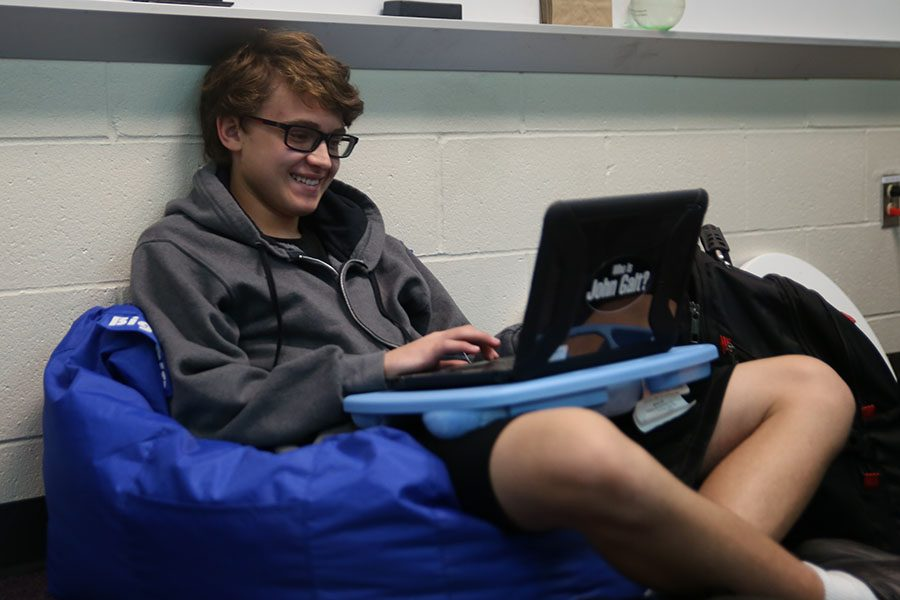 """Laptop on his legs, Benjamin Wiseman (9) analyzes the Lincoln-Douglas court case during speech and debate's after school meeting, Sept. 25. """"I thought speech and debate would be interesting,"""" Wiseman said. """"I am in ALARP (Advanced Language and Research/Presentation), so I wanted to include more of speech related things into my life. I think public speaking is an important skill. Also, it is useful to convey a concept clearly so you can persuade people to your point of view. We haven't gotten too far in speech and debate yet, but the best part has been being able to analyze the case and choosing values that are important to us."""""""
