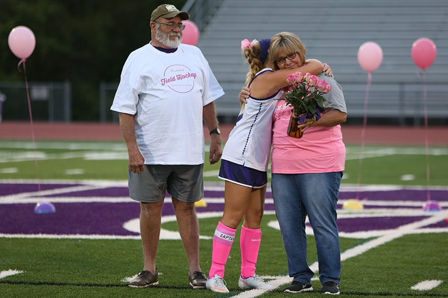 Pink+surrounding+the+field%2C+Ed+Riiff%2C+husband+of+Pamela+and+grandfather+of+Hannah+Daffron+watches+on+as+Daffron%2C+varsity+field+hockey+captain+and+granddaughter+of+Riiff%2C+hugs+Pamela+Riiff%2C+varsity+field+hockey+assistant+coach%2C+during+a+halftime+ceremony+honoring+Pamela+as+she+continues+to+battle+breast+cancer.+Riiff+has+been+coaching+field+hockey+for+4+years.+%E2%80%9CI+thought+to+myself+%E2%80%98Why+are+the+girls+wearing+all+this+pink%3F%E2%80%99+then+Hannah+said+to+me%2C+%E2%80%98We+are+doing+different+things+this+year%2C%E2%80%99+and+then+it+clicked%2C+the+pink+was+for+breast+cancer%2C%E2%80%9D+Pamela+Riiff+said.+%E2%80%9CIt+was+extremely+heartwarming+feeling.+The+best+thing+in+the+world+is+having+these+girls+who+care+for+you.+Cancer+is+one+of+the+worst+things+in+life%2C+but+having+these+girls+who+care+for+you%2C+it+takes+all+your+problems+away.+I+have+made+a+connection+with+each+and+every+one+of+these+girls.+I+try+to+have+fun+and+listen+to+them+and+get+to+know+them+outside+of+the+sport.%E2%80%9D
