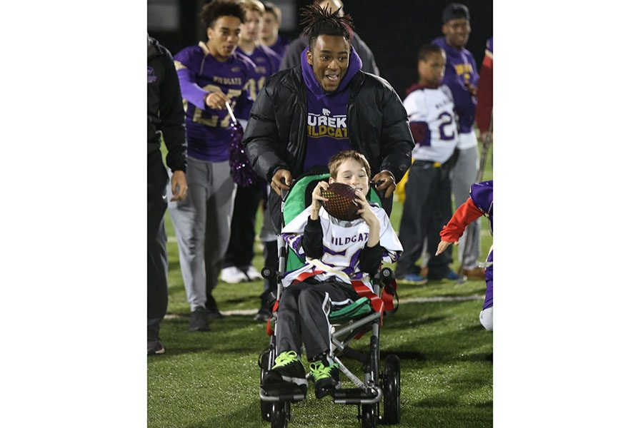 "Friday night lights started, Caleb Warren, varsity football, pushes his buddy, Noah Grobe, during the Best Buddies Friday Night Lights football game, Oct. 19. This event allows students with developmental and intellectual disabilities to experience a friday night football game. ""I think friday night lights is fun to participate in because you take part in something that is bigger than you,"" Warren said. ""My favorite part was seeing Noah so happy when he made touchdowns. It allowed me to see how much I can do and how I should be grateful for everything.."""