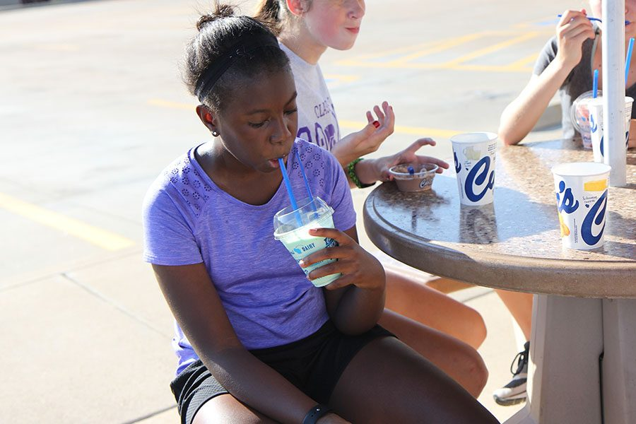 "Almost 2 mile run over with, Mikayla Gregory (9) drinks a milkshake from Culver's after cross country's Culver's run, Oct. 2. ""I liked running with my friends,"" Gregory said. ""It was fun to be able to talk the whole time. We warmed up around the softball fields, then jogged to Berry Park, then started the run to Culver's. The run is something cross country has done this before. I did cross country because during the summer, I thought 'I am not doing anything, why not do cross country?' So I went to the practices and then joined the team. The community is great and it helps me be healthier. I am trying to play basketball in the winter, so this helps me stay in shape for that. I have made a lot of friendships with other classmen and with most of the freshmen on the team. The people I didn't know were really nice to me and supportive."""