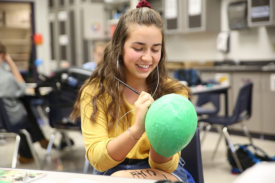 """Halloween approaching, Rebecca Sacco (10) paints her papier-mâché alien during Art Club after school, Oct. 30. """"My papier-mâché balloon turned out weird,"""" Sacco said. """"Halloween was the day after, so the alien fit the theme. The best thing about Art Club is being able to hang out with my friends and create weird things together. After a long day, art is just a way to just relieve stress. It is a great way to be creative."""""""