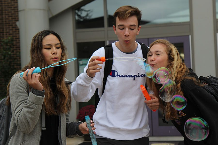 "Bubble wand in their hands, Grace Munton, Drew Derickson and Sydney Groff (10) blow bubbles for Student Council's Bubble Friday in the front of school before classes begin, Oct. 12. ""I like Bubble Friday because it is really fun and I can be there with my friends,"" Munton said. ""It's awesome to just welcome everyone into school that day. It makes people happy because they're always smiling and they try to pop the bubbles. It is important to have that close community because it makes everyone feel welcome. It is easier to just be around everyone then and there is no awkwardness."""
