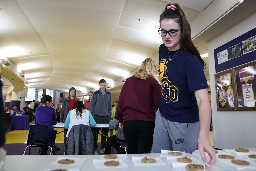 "Cookie within reach, Regan Inglis (12) takes her reward provided during lunch by Renaissance for having a 3.0 or higher grade point average, Nov. 12. ""I have always struggled a little bit with school, so to be rewarded for my grades isn't something I usually get,"" Inglis said. ""The students work so hard, and some students go home and no one recognizes their achievements. To get that recognition, especially from our principals, it felt awesome. I liked the cookies, but I liked the popcorn and candy mix more from last time they gave out rewards. I just like the sweet and salty mix better than just sugar."""