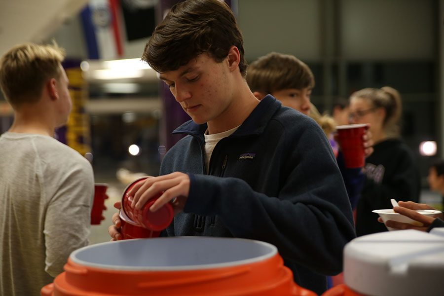 """Chili cooked, Stephen Beeler (12) grabs a drink during the Fellowship of Christian Athletes chili cook-off, Nov. 13. """"I liked being together with people that I know and some people that I didn't. It brought all sorts of people together,"""" Beeler said. """"My youth pastor Elliot Vorgis came to speak with us, and it was fun getting to hang out with him. It was special having Elliot here because I have known him for a while and we have gotten close over the years. I have a deeper connection with him. It was cool bringing someone from my life outside of school into school. It got to show my school friends my church pastor. FCA allows me to connect with other Christians and Catholics in the school. Sometimes I don't even know who they are until they come to FCA. It is cool getting to know them. Whenever I am walking the halls and going to class, I see them and know we have something in common."""