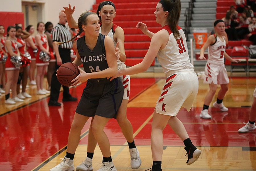 "Up against competition, Kennedy Demoulin, forward, looks for someone to pass to during the girls varsity basketball game against Kirkwood, Dec. 11. ""During the game, we had a lot of mistakes, but we also had a lot of successes,"" Demoulin said. ""During practice, we are working on improving those mistakes, but also focusing on what we did right so we can continue that. I enjoy the girls on the team. It is always fun. We connect well. Each game, we get so much better, and it is awesome seeing our improvement. The trust we have in each other on the floor improves when we have those good relationships. The way we share the ball becomes better, too."" The Wildcats lost, 42 to 56."
