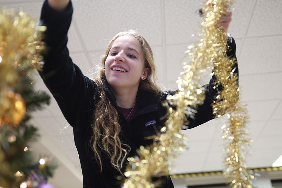"""Tinsel being hung, Savannah Lesher (11) decorates holiday trees in the commons with StuCo after school, Dec. 3. """"The holiday trees brings everyone together,"""" Lesher said. """"It doesn't matter what religion or who you are, everybody can come together this time of the year and have a fun time. It exemplifies that everybody has different beliefs. They're holiday trees so everybody can be involved."""""""