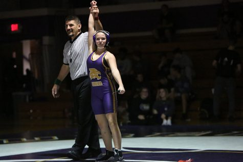 Making history, Sydney McFadden gets her arm raised after winning her match against Seckman during the first ever girls wrestling team match, Nov. 28.
