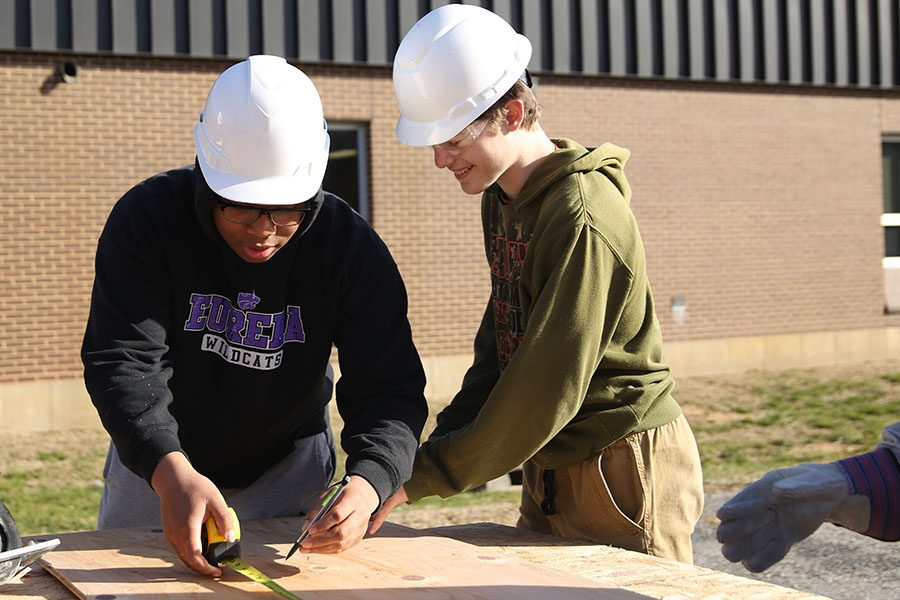 "Tiny house coming along, Jadin Wallace-Grayer and Michael Jones (10) measures wood to cut in Gary Schneider's sixth hour Geometry in Construction class, Jan. 10. ""I took Geometry in Construction because I wanted to learn how to use geometry in everyday life. My favorite part is doing the construction and learning how to use the tools. It is exciting learning stuff like that,"" Wallace-Grayer said. ""Since we're building a tiny house, it feels great knowing I will be able to be a part of something that will benefit someone else. I like having a part in something like that."""