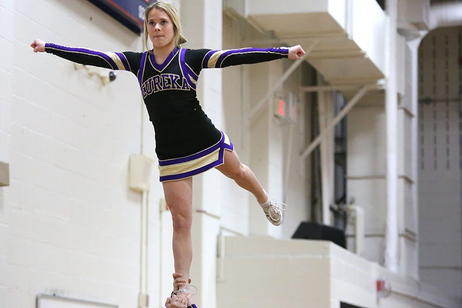 """Game starting, Sophie Krause, flyer, performs the beginning of the game routine with varsity cheer during the boys varsity basketball game at Parkway South, Jan. 18. """"I enjoy my team. We are all so close. It makes it fun,"""" Krause said. """"We always help each other out. It is a team sport. I have been cheering since the 5th grade. I keep doing cheer because we have a goal every year. We keep pushing ourselves so that at every competition we are better. I prefer to cheer at football games. I like to watch the game. Also, it is easier to cheer with a bigger crowd and more people go to football games."""""""