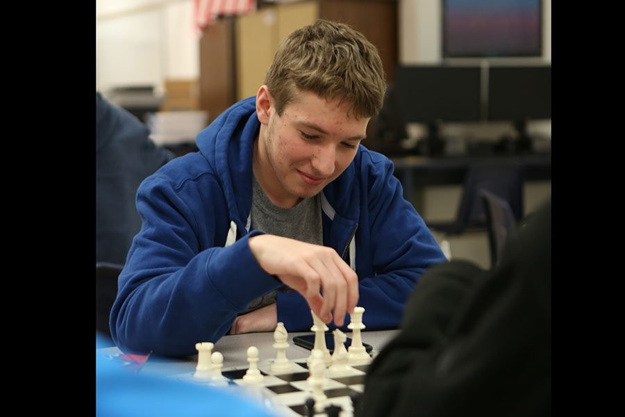 """Time for his move, Tyler Branscum (11) looks to move a piece during chess club after school, Jan. 23. """"I joined chess club because a lot of my friends are in,"""" Branscum said. """"I like the consistency of doing chess club every week. I enjoy playing chess."""""""