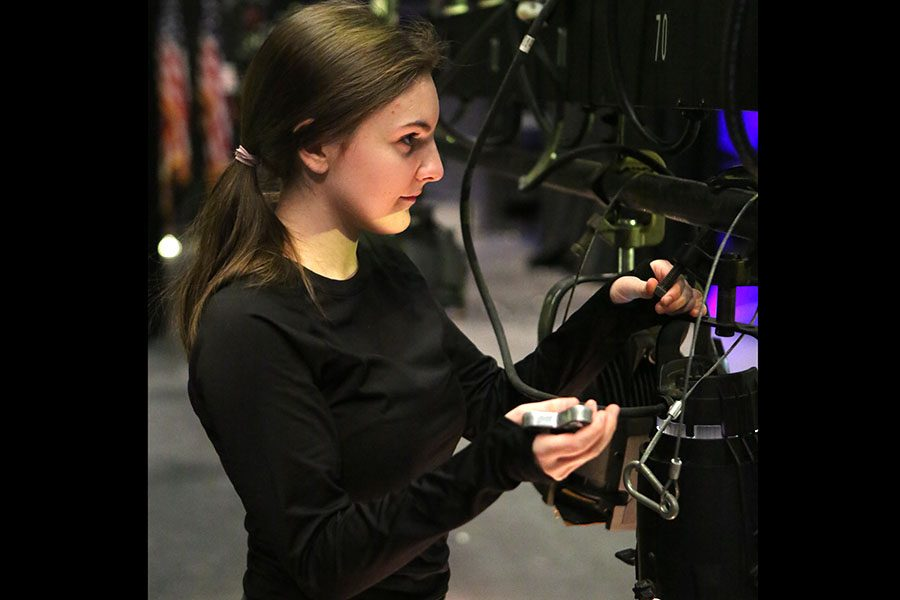 "Stage plan done, Jenna Nicholas (11) attaches a light bulb during Mr. EHS stage preparations after school, Jan. 24. ""We are working on the specials lights so when the 6 contestants who make it to the finals, they will all have lights on them,"" Nicholas said. ""I do both tech and acting, but when I do tech I like how it influences the production. It adds so much to the show. If even one person messes up the lighting, the show loses credibility no matter how good the actors are. I am most excited for seeing who wins Mr. EHS. It is always exciting to see who is going to win."""