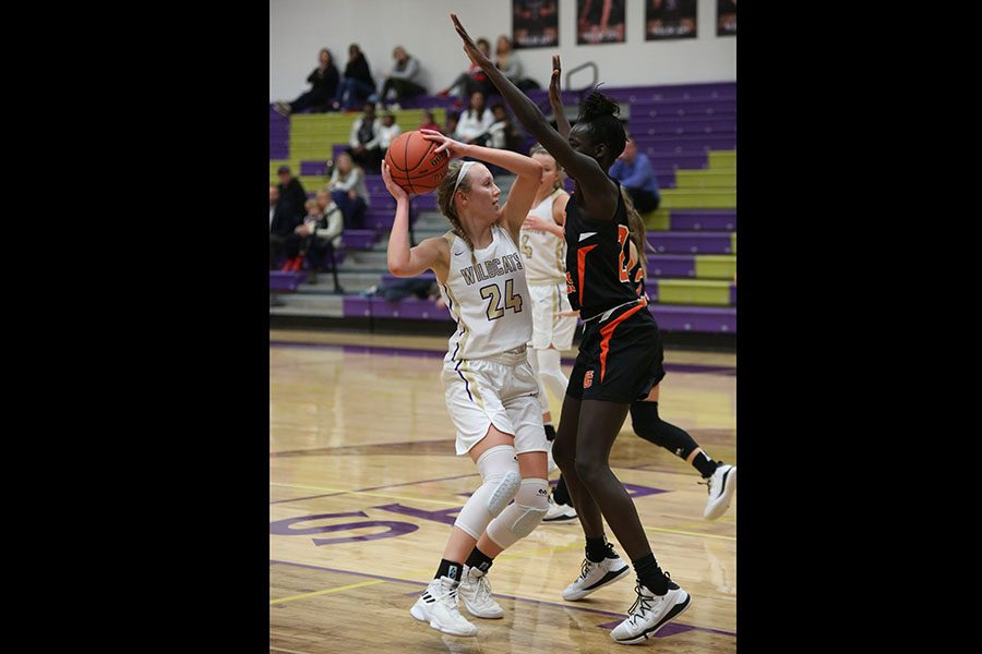 "Trying to shoot, Kennedy Demoulin attempts to get around her Webster Groves opponent during the girls varsity basketball game, Jan. 9. ""Ever since I was 10, I've played and I've played all three years of high school. I like the intensity of it and the aggressiveness that we have as a team,"" Demoulin said. ""I also like all of the girls on the team, they're sweet and fun to be around. I think that was on of my best games that I've had all season. They were a really tough team to play against, but we fought back. We ended up losing, but we could have definitely won."" The Wildcats lost."