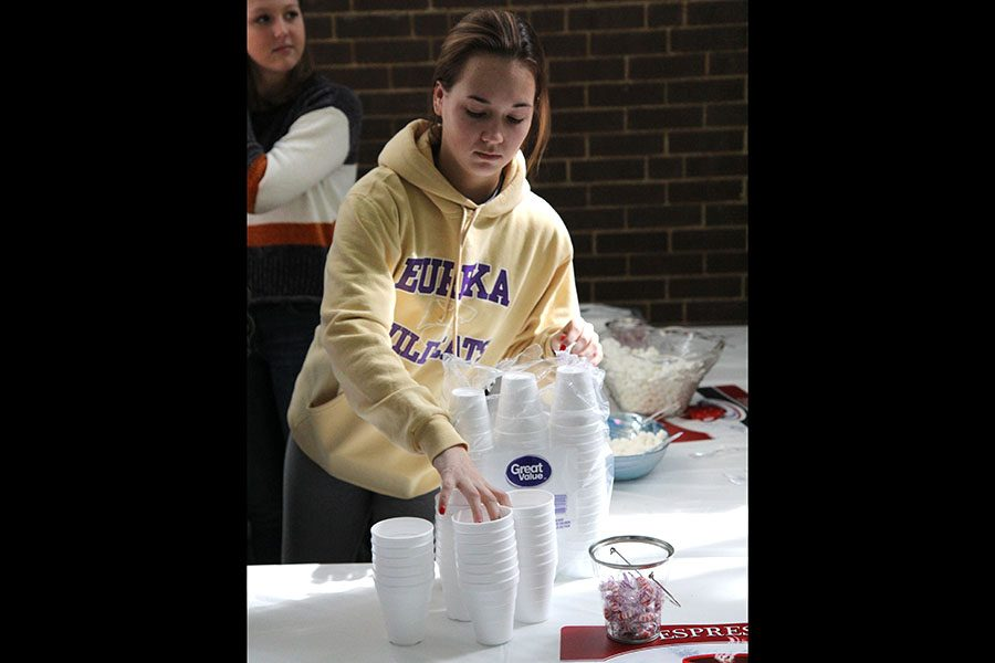 "Cups being set, Madeline Reisig (12) sets up for the E!Crew hot chocolate lunch for freshman, Feb. 21. ""All of the executives of E!Crew scheduled the event. We got the grant and just planned it out,"" Reisig said. ""Second semester is harder. Everyone gets sick of school and it can be hard for them to keep their focus. E!Crew gives the freshmen their first group to connect with and that is important."""