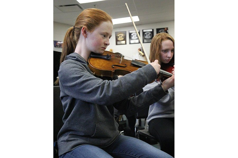 "Plucking the strings, Kyli Smith, violin, plays 'Mock Morris' by Percy Grainger during Mary White's sixth hour symphonic orchestra class, March 1. ""Before I came into the Rockwood School District, I lived in a place where we didn't have orchestra in our schools,"" Smith said. ""I had to take private lessons to play. I did some summer camps before sixth grade and have kept doing it since middle school. I have always liked music. Before starting the violin, I played piano for around 10 years. I saw people play violin and I just knew it was what I wanted to play. At first, it was frustrating because it was hard to learn. Eventually, I met great teachers who motivated me to keep going and get better as a player."""