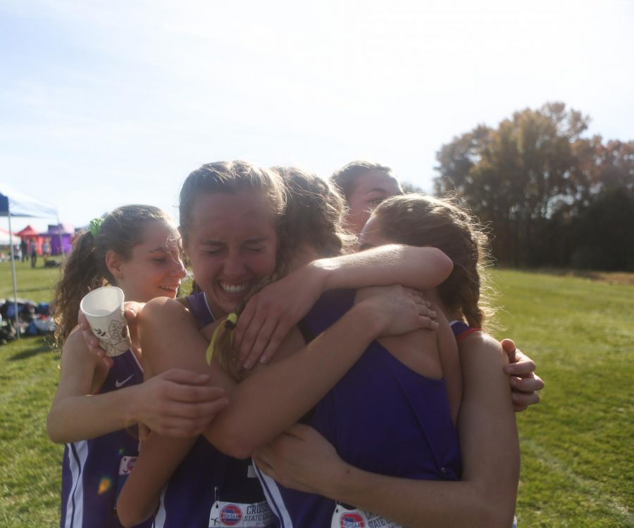 Following the earning of third place at state, the Eureka girls cross country team embraces in a group hug, Nov. 9.