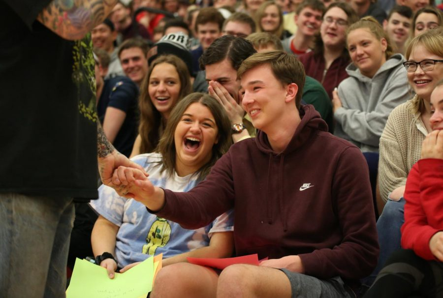 Hands being held, Davey Muise talks to Andrew Derickson (11) about his story during the suicide prevention assembly, March 25.