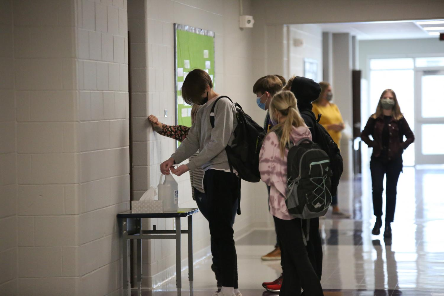 Students wear masks and use hand sanitizer before entering a class room, Nov 13.