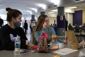 Maddie Kacer (11) and Oliva Crain (11) sit at the lunch tables now limited to five students.
